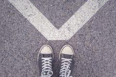 站立在都市路面的V形的标志上 免版税库存照片