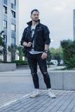站立在都市风景背景的黑牛仔裤夹克的年轻可爱的人 免版税库存图片