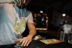 站立在酒吧的酒吧后的白色T恤的男服务员专家和做一个可口酒精鸡尾酒用苹果 免版税库存照片