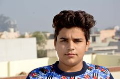 站立在采取的sunbath房子屋顶的十几岁的男孩 免版税库存照片
