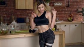 站立在重量控制的电子等级的年轻女人脚在厨房 体育制服的逗人喜爱的适合的妇女 股票录像