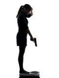 站立在重量标度绝望的妇女瞄准枪剪影 免版税库存照片