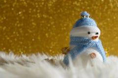 站立在金子冬天圣诞节雪背景中的愉快的雪人 圣诞快乐和新年好贺卡与拷贝空间 免版税库存照片