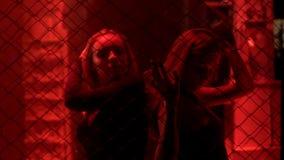站立在金属在红灯,夜生活的链子篱芭后的两个性感的夫人 免版税库存照片
