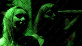 站立在金属在绿灯,夜生活的链子篱芭后的邀请的妇女 库存照片