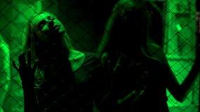 站立在金属在绿灯,非法事务的链子篱芭后的性感的夫人 免版税库存图片
