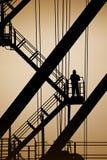 站立在金属步的剪影的孤立人工业梯子 免版税库存照片