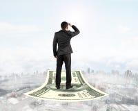 站立在金钱飞毯的商人观看前面 免版税库存照片