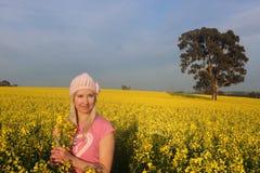 站立在金黄油菜农场的领域的妇女 免版税库存图片
