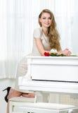 站立在钢琴附近的女性钢琴演奏家画象 图库摄影