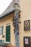 站立在铁匠铺旁边的柱子,装饰用面貌古怪的人和散布与各种各样的锻件项目在锡比乌市在罗马尼亚 库存图片