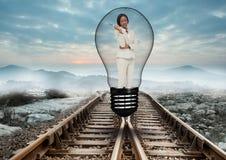 站立在铁路轨道的电灯泡的美丽的妇女反对天空 库存照片