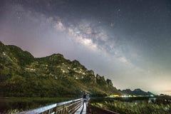 站立在银河和山,泰国中的一个人 免版税库存照片