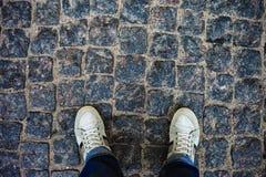 站立在铺路石的运动鞋的少年人 免版税图库摄影