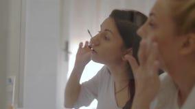 站立在镜子前面早晨和申请构成的室内的射击两年轻女人的 股票视频