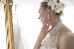 站立在镜子前面的新娘 库存图片