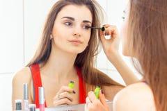 站立在镜子和油漆睫毛染睫毛油前面的年轻美丽的浅黑肤色的男人 免版税图库摄影