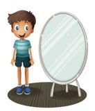 站立在镜子旁边的男孩 库存照片