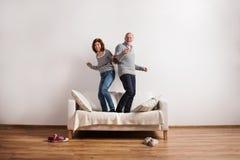 站立在长沙发的美好的资深夫妇,跳舞 美丽的夫妇跳舞射击工作室妇女年轻人 库存图片