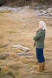 站立在长的草的资深妇女 免版税库存图片