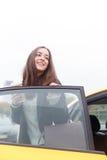 站立在门户开放主义的微笑的浅黑肤色的男人汽车 免版税库存图片