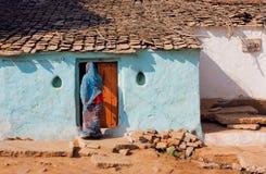 站立在门的可怜的家庭和印地安妇女议院  免版税库存照片