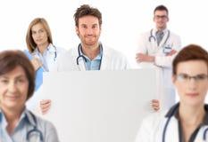 站立在队的医生拿着空白纸 免版税库存图片