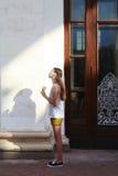 站立在阳光下的女孩在大厦附近 免版税库存照片
