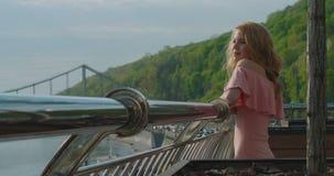 站立在阳台和享受美丽的河的看法的可爱的迷人的白肤金发的女孩的画象和 影视素材