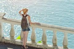 站立在阳台和看海的帽子的女孩 backarrow 库存照片