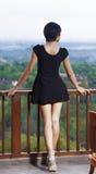 站立在阳台的女孩,倾斜他的手在栏杆  免版税库存图片