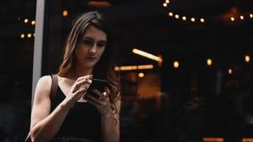 站立在陈列窗附近和使用智能手机,走和浏览互联网的年轻美丽的妇女 影视素材