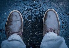 站立在降雨量期间的水坑中间 库存照片