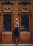 站立在雍容姿势的美丽的妇女在葡萄酒门附近 免版税库存照片