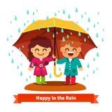 站立在雨中的男孩和女孩在伞下 图库摄影