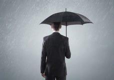 站立在雨中的年轻聪明的busienssman 库存图片