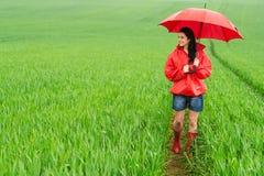 站立在雨天的微笑的少妇 库存照片