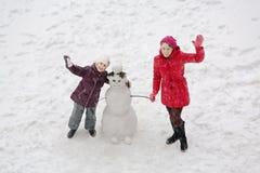站立在雪人旁边的微笑的母亲和女儿 库存图片