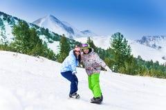 站立在雪板平衡的两个朋友 库存照片