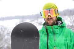 站立在雪板的雪和在protectiv的年轻人 库存照片