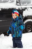 站立在雪的一辆汽车前面的小男孩 免版税库存照片