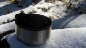 站立在雪的通入蒸汽的杯子热的茶或咖啡在森林里 股票录像