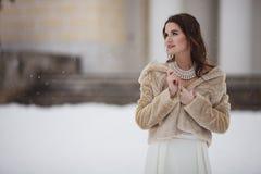 站立在雪的eco皮大衣的女孩 免版税库存照片
