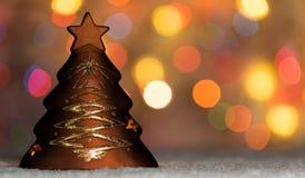 站立在雪的Xmas树型蜡烛台,与圣诞树光、bokeh背景和拷贝空间 免版税库存照片