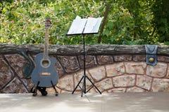 站立在露天舞台的声学吉他在篱芭附近 库存照片
