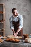 站立在面包店的愉快的年轻人面包师切了面包 免版税图库摄影