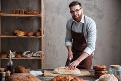 站立在面包店的愉快的年轻人面包师切了面包 免版税库存图片