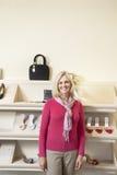 站立在鞋店的鞋类前面的一名成熟妇女的画象 库存照片
