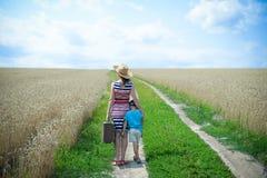 站立在领域之间的路的女性和孩子  库存照片