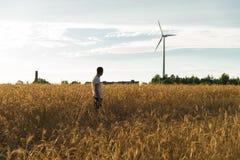站立在领域的一个人看造风机 库存图片